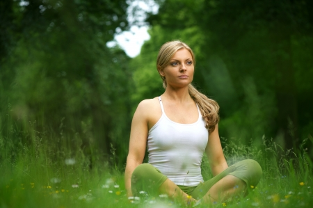 Portrait of a beautiful young woman sitting in yoga pose in the forest photo