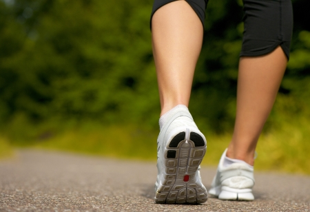 Female walking outdoors in running shoes from behind Stock Photo - 20952556