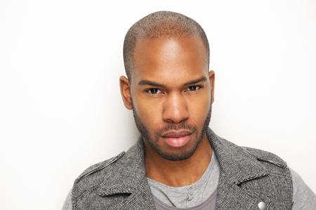 ojos marrones: Cerca de retrato de un hombre negro joven atractivo contra la pared blanca