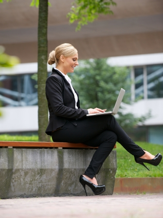 laptop outside: Portrait of a happy businesswoman working on laptop in the city