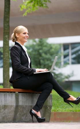 Portrait of a businesswoman smiling and working outdoors on laptop photo