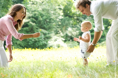 walk in: Portrait of a happy young family teaching baby to walk in the park