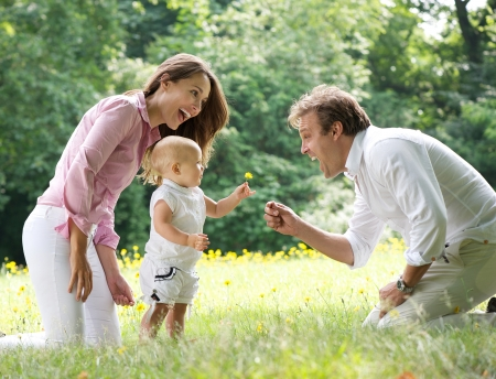 Portrait of a happy family with child giving flower to father int he park photo