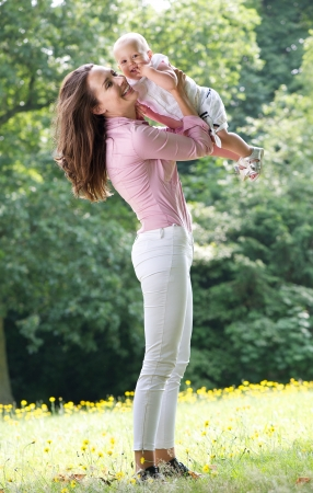 Portrait of a beautiful woman holding baby in park photo