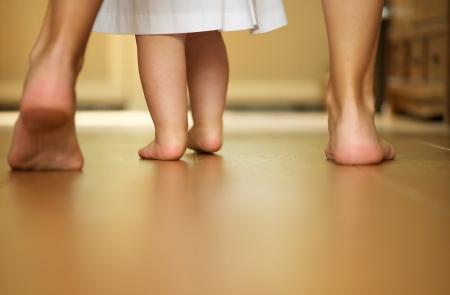 Close-up portret van een moeder lesgeven baby om binnenshuis te lopen