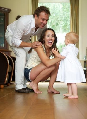 Retrato de una pareja de padres felices ayudando bebé toma primeros pasos