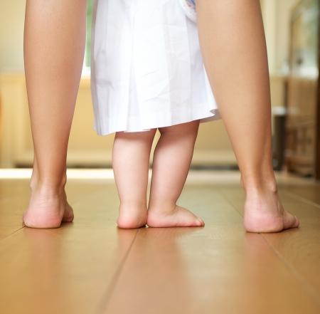 piedi nudi di bambine: Closeup ritratto di una madre aiutare bambino a camminare al chiuso Archivio Fotografico