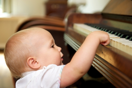 Portrait of a cute baby playing on piano photo