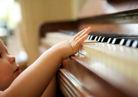 pianista: retrato de cerca de un beb� tocando el piano Foto de archivo