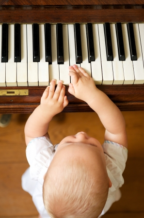 Portrait of a cute baby playing piano - from above photo