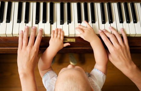 teaching music: Closeup portrait of a baby learning to play piano with mother - from above