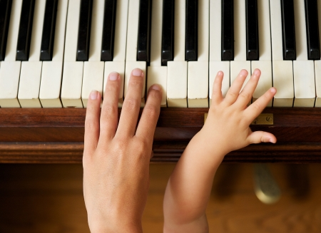 Closeup portrait of an adult hand playing piano with baby hand photo