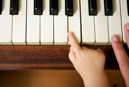 Closeup portrait of a baby hand playing piano with adult hand photo