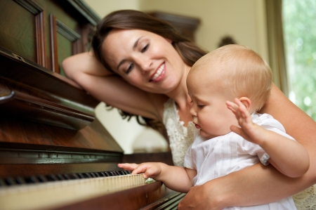 love music: Portrait of a happy mother smiling as baby plays piano  Stock Photo