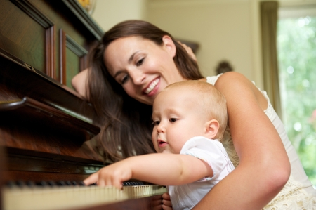 teaching music: Portrait of a mother smiling as baby plays piano