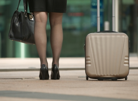 the girl in stockings: Business woman standing with bag and suitcase on pavement