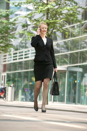 Portrait of a businesswoman walking and talking on mobile phone in the city Stock Photo - 21175763