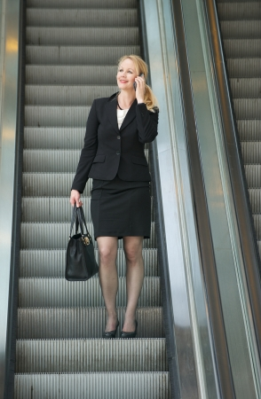 Portrait of a businesswoman talking on phone on escalator photo