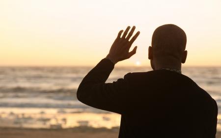 Portret van een man zwaaien naar de zonsondergang Stockfoto