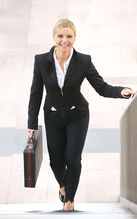 upstairs: Portrait of a businesswoman smiling and walking upstairs with briefcase