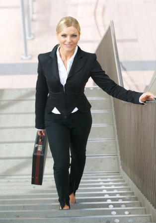 upstairs: Portrait of a confident business woman walking upstairs with bag Stock Photo