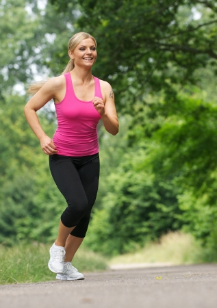 Portrait of a happy young woman jogging outdoors photo