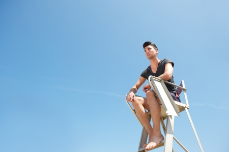 Portrait of a lifeguard sitting on elevated chair