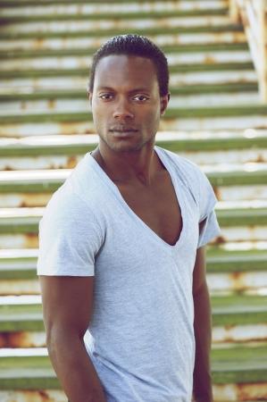 negro: Retrato de un ser hermoso hombre negro de pie al aire libre