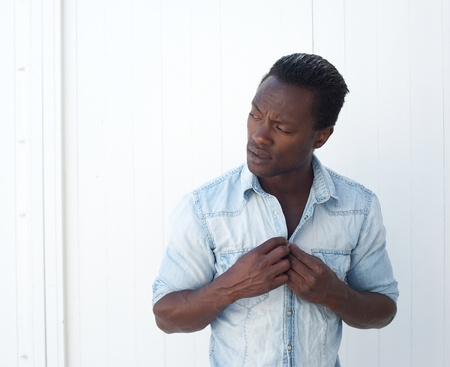 buttoning: Closeup portrait of a young black man adjusting shirt button outdoors against white background Stock Photo