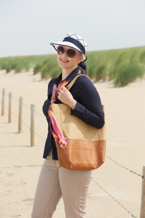 Portrait of an older woman smiling at the beach with sunglasses and bag photo