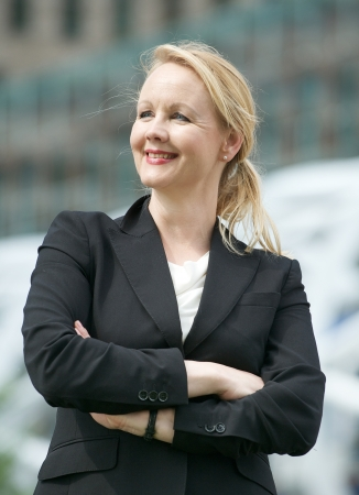 Portrait of a happy business woman standing outside the office with arms crossed photo