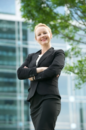 Portrait of a businesswoman smiling outdoors with arms crossed photo