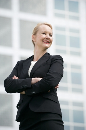 Closeup portrait of a successful businesswoman smiling outside office building photo