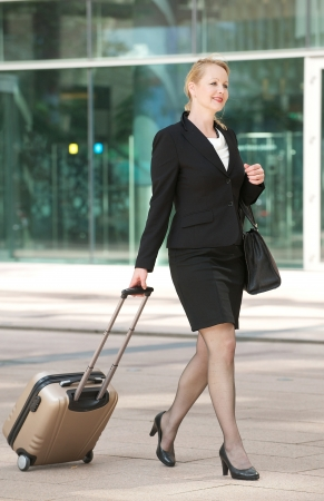 int: Portrait of a business woman walking int he city with travel bag and luggage