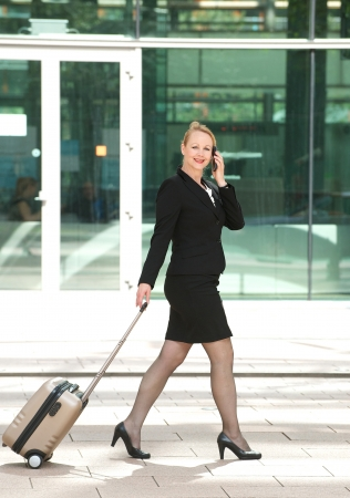 Portrait of a businesswoman walking and talking in the city with mobile phone and travel bag Stock Photo - 21371528