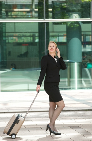 Portrait of a business woman walking and calling with mobile phone outdoors photo