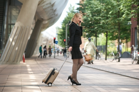 Portrait of a businesswoman traveling with luggage and mobile phone photo