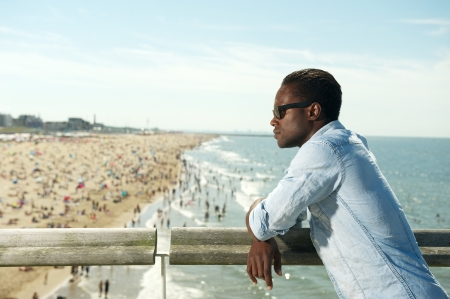 Horizontal portrait of a handsome black man with sunglasses relaxing at the beach photo