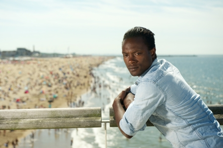 Portrait of an african american man relaxing at the beach on a summer day photo