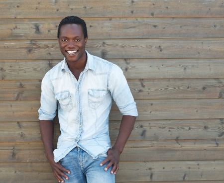 african american male: Portrait of a handsome african american man smiling outdoors with hands in pocket Stock Photo