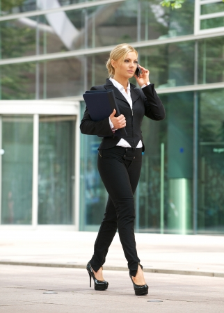 Portrait of a business woman walking and talking on cellphone in the city photo