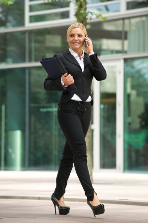 Portrait of a beautiful business woman talking on mobile phone outside the office photo
