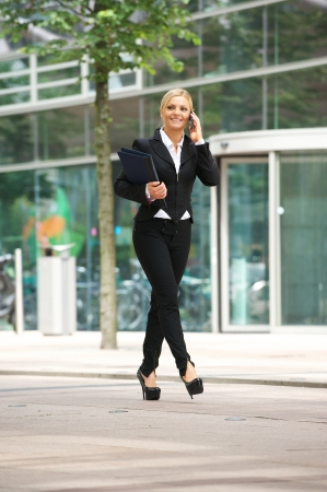 Portrait of a happy business woman walking outdoors and talking on mobile phone photo