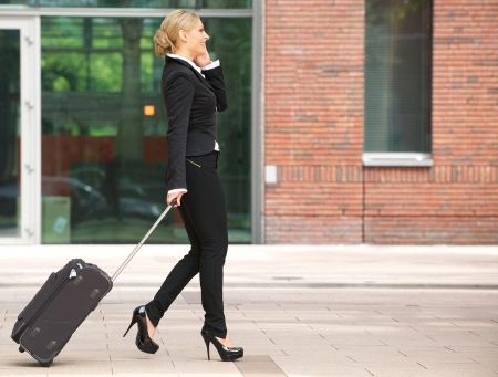 Profile portrait of a business woman walking with luggage and talking on phone photo