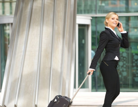 Portrait of a happy businesswoman walking with suitcase and talking on mobile phone photo