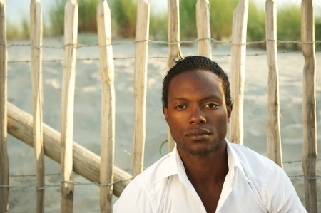 Portrait of a handsome african man sitting outdoors alone photo