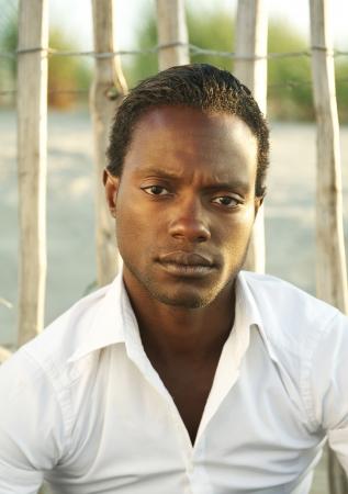 Closeup portrait of a handsome black man in white shirt  photo