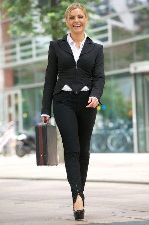 business briefcase: Full length portrait of a business woman walking in the city with briefcase