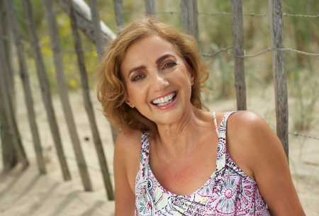 middle aged woman smiling: Closeup portrait of an attractive middle aged woman smiling outdoors Stock Photo