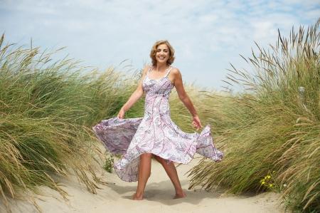 attraktiv: Porträt einer schönen Frau mittleren Alters tanzt im Sand am Strand Lizenzfreie Bilder